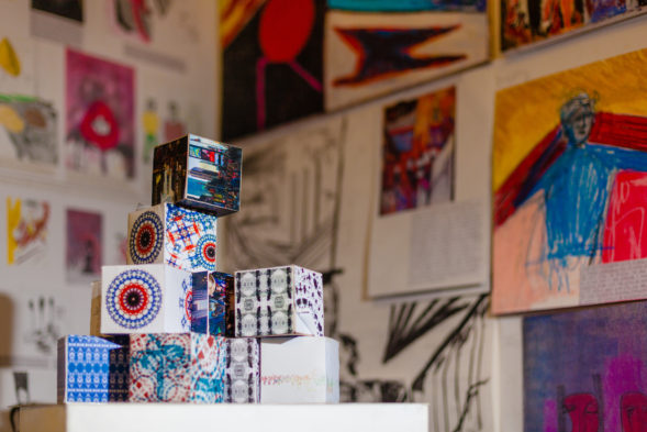 Art project - Decorated boxes stacked in a pyramid shape in front of a blurred background of artwork