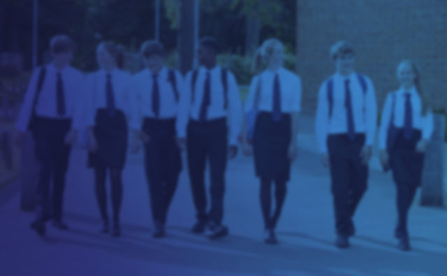 Group Of Teenage Students In Uniform Outside School Buildings