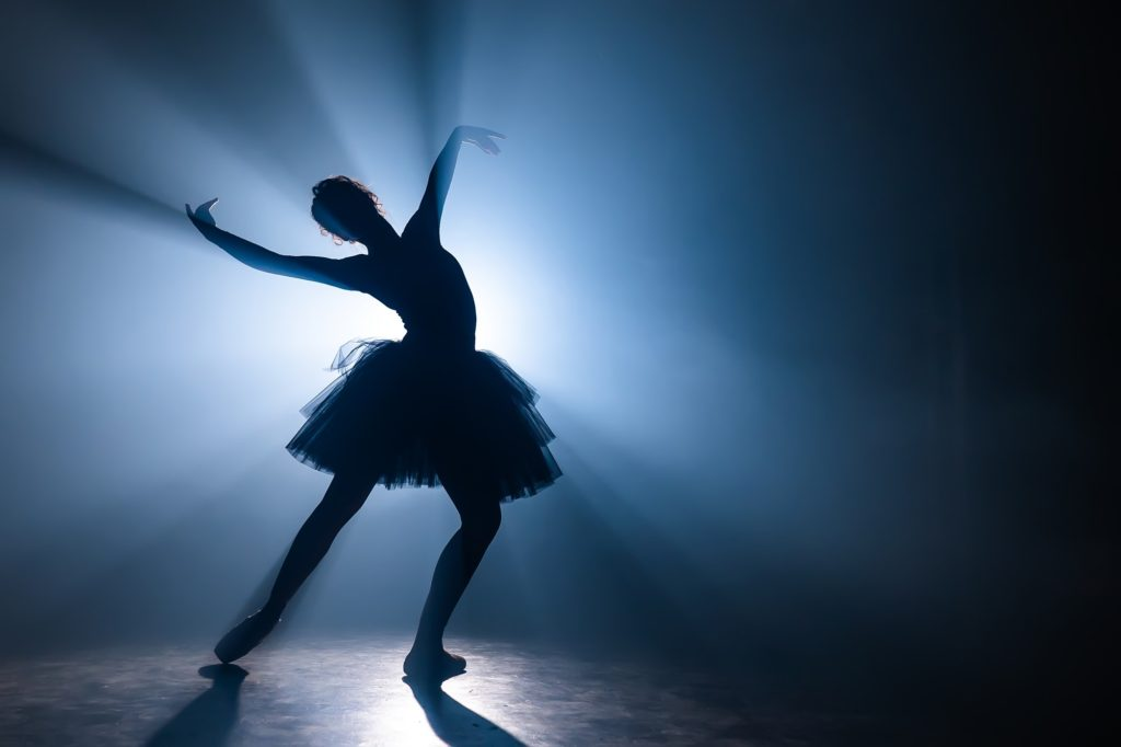 Solo performance by ballerina in tutu dress against backdrop of luminous neon spotlight in theater.