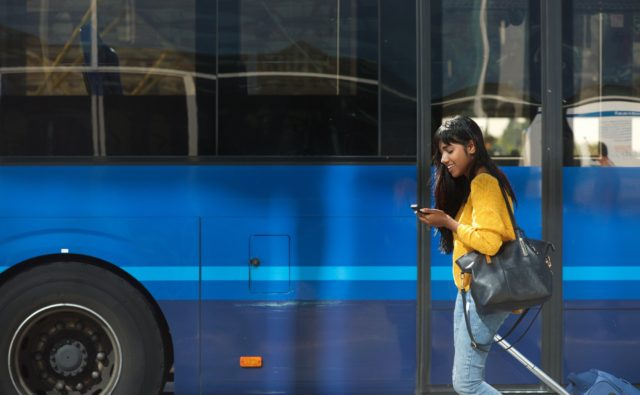 smiling young Indian woman walking with suitcase and cellphone by bus station